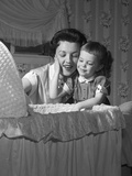 1950s Mother and Daughter Admiring Baby in Bassinet
