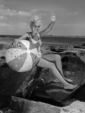1960s Smiling Blond Teenage Girl Sitting on Rocky Shore Holding a Beach Ball Waving