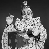 1960s Clown in Polka-Dotted Outfit Taking Picture with Old-Time Camera Holding Birdie