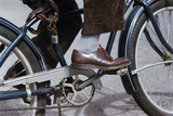 Man Riding Bicycle in Dress Shoes