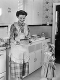 1950s Mother in Kitchen Showing Cake to Daughter Kitchen
