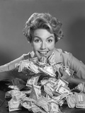 1950s-1960s Smiling Woman Scooping Up Pile of Money Bills Cash