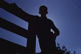 Silhouette of Boy Leaning Against Fence