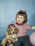 1950s-1960s Little Girl in Party Hat Sitting Holding a Cocker Spaniel Puppy