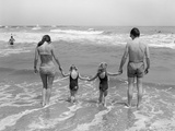 1970s Family on Vacation at Ocean Beach Holding Hands Walking on Sand in Surf