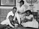 1960s African-American Family Counting Change in a Piggy Bank