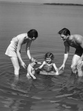 1930s Family Father Mother Daughter Son with Rubber Inner Tube Wading in Seashore Water