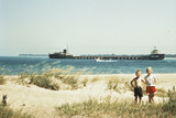 1950s Young Boy and Girl on Beach Smiling with a Tanker Ship on Lake