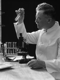 1920s-1940s Scientist Lab Technician in White Coat Looking at Test-Tube in Front of Microscope