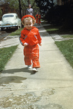 1950s Little Boy in Red Outfit Running on Pavement with Mother Just Behind