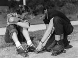 1950s Teen Boy Helping Girl Put on Metal Roller Skates Sitting on Sidewalk