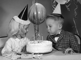 1960s Boy Blowing Out Candles on Birthday Cake