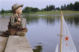 Boy Sitting by Lake in Cowboy Hat