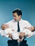 1960s Father Holding Twin Babies Infants Looking Down at One of Them