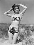 1950s Smiling Young Woman Kneeling in Grassy Sand Wearing Polka Dot Bikini Shading Eyes from Sun