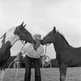 1960s Boy Wearing Cowboy Hat Holding Harness of 2 Horses One on Either Side of His Face Kissing Him
