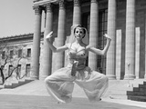 1960s Woman in Middle Eastern Belly Dance Costume Jumping in Front of Building