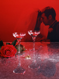 1960s Champagne Flutes with Rose and Wedding Rings in Red Filter with Couple in Background