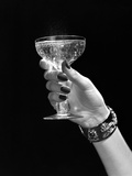 1930s-1950s Woman Hand Ornate Metal Bracelet Holding Up New Year Toast Glass of Champagne