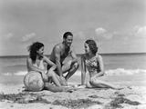 1930s-1940s Two Women One Man in Bathing Suits Sitting on Beach