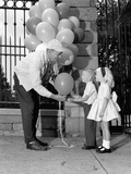 1960s Children Boy Girl Getting a Balloon from Man