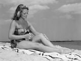 1950s Woman in Strapless One-Piece Bathing Suit Seated on Beach Towel Putting on Suntan Lotion