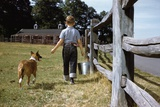 Boy and His Dog Walking Along a Fence