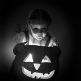 1950s Little Girl Standing over Carved Pumpkin Face Lit by Candle