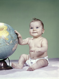 1960s Smiling Baby Girl Sitting in Diapers Hand Touching World Globe