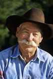 1990s Portrait of Smiling Cowboy with Gray Mustache Black Hat Blue Shirt