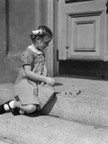 1930s-1940s Child Little Girl Sitting on Stoop Playing Jacks