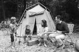 1970s Family of Four Sitting in Front of Tent in Woods  Son Holding Fishing Pole and Big Fish