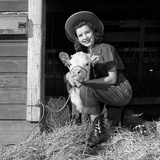 Girl Posing with Calf in Straw Filled Stall in Barn