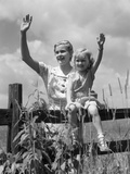 1930s Girl Sitting on Fence with Woman Next to Her in Field Waving