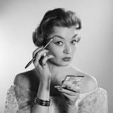 1950s-1960s Woman Applying Makeup Eye Brow Pencil Holding Compact Mirror