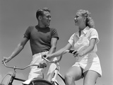 1930s-1940s Smiling Blonde Couple on Bikes Looking at One Another
