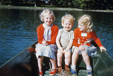 Boy and Two Girls in Red Sweaters Sitting in Back of Rowboat