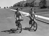 1950s Teen Boy Girl Couple Riding Bikes Down Residential Street