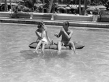 1930s-1940s Couple Drinking While Floating in a Pool on a Rubber Raft at Florida Resort