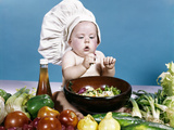 1960s Baby Making Salad Wearing Chef Hat with Variety of Fresh Ingredients Vegetables