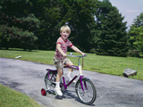 1960s-1970s Young Blond Boy Riding Bike with Training Wheels