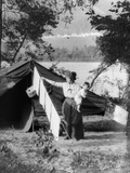 1920s Mother Holding Baby on Hip as She Checks Laundry Diapers Hanging on the Line in Front of Tent
