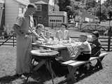 1950s Family in Backyard Cooking Hot Dogs Sitting at Picnic Table