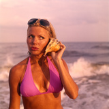 1970s Pouting Sexy Woman in Lavender Bikini Near Beach Holding Seashell to Ear Listening to Ocean