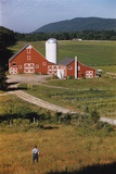 Boy Standing in Field Near Red Barn