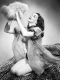 1950s Young Woman Wearing Sexy Lingerie Kneeling on Leopard Skin Holding Fluffy Dog