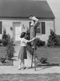 1950s Children Boy and Girl Playing with Stilts Standing Walking on Sidewalk
