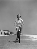 1940s Summer Time Smiling Blonde Woman Riding Bike on Seashore Beach Boardwalk Directly