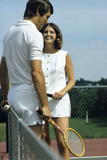 1970s Smiling Couple Standing by Net on Tennis Court Holding Wood Rackets