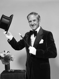 1970s Smiling Man Magician Wearing Velvet Tuxedo White Gloves Pointing Magic Wand at Top Hat